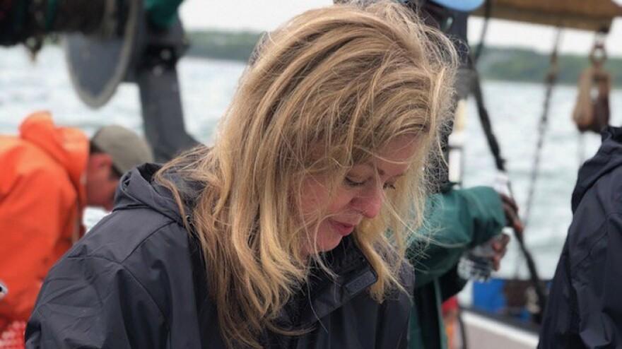 Melissa Ross measures flounder on a trawler in Narragansett Bay.