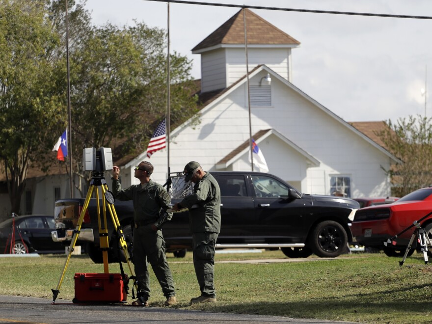 Law enforcement officials investigate the scene of a shooting at the First Baptist Church of Sutherland Springs on Tuesday in Sutherland Springs, Texas.
