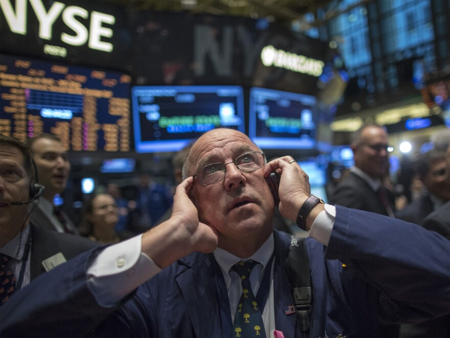 JPMorgan Chase trader Frederick Reimer works on the floor of the New York Stock Exchange. The government's monthly jobs numbers won't be released as scheduled Friday, leaving financial markets without key data to evaluate the economy.