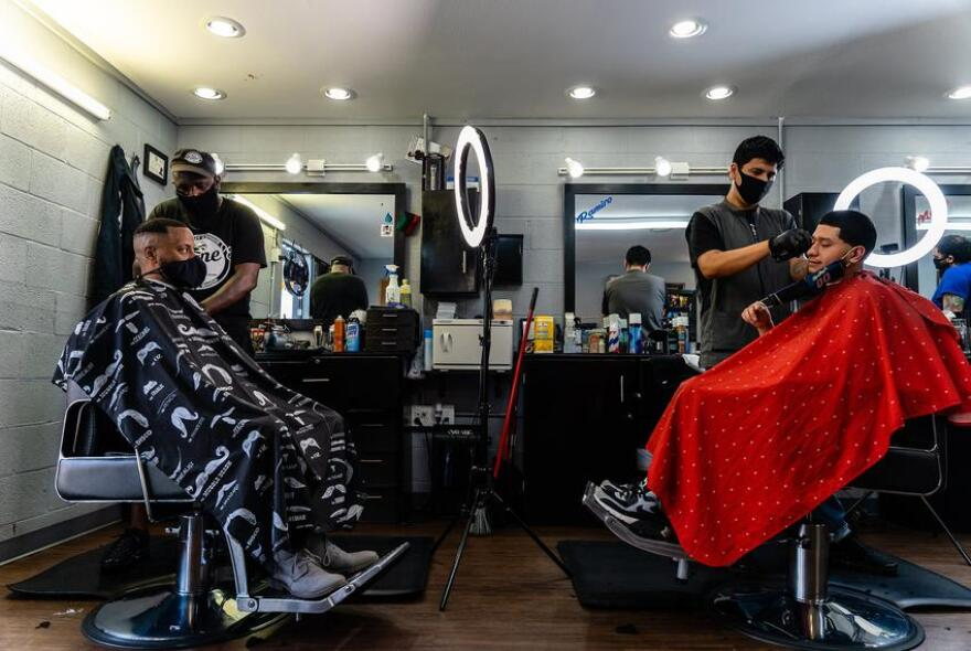 two barbers serving respective clients