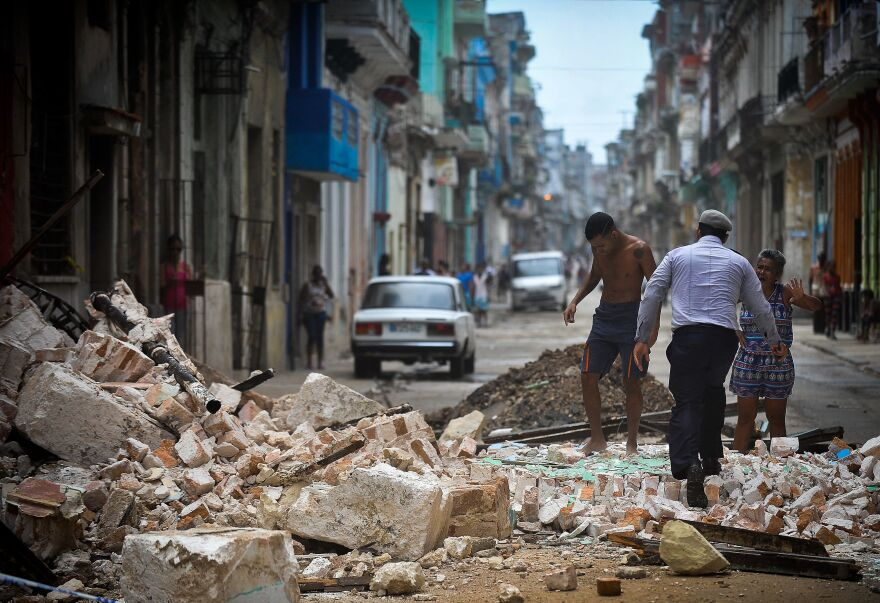 Cubans wade through the rubble from a collapsed building in Havana, on Saturday. The Cuban government extended its maximum state of alert to three additional provinces, including Havana, amid fears of flooding in low-lying areas.
