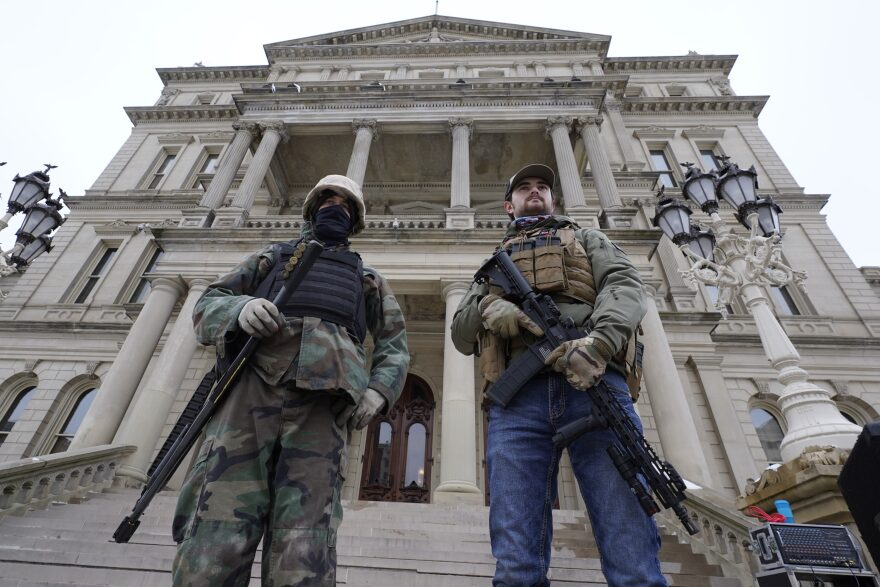 Armed men stand on the steps at the State Capitol after a rally in support of President Trump in Lansing, Michigan, on Jan. 6, 2021. (Paul Sancya/AP)