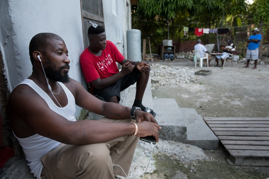 Odne Laguerre (left) and evacuee Bobson Timothee pass the time while other evacuees play cards at the Laguerre home.