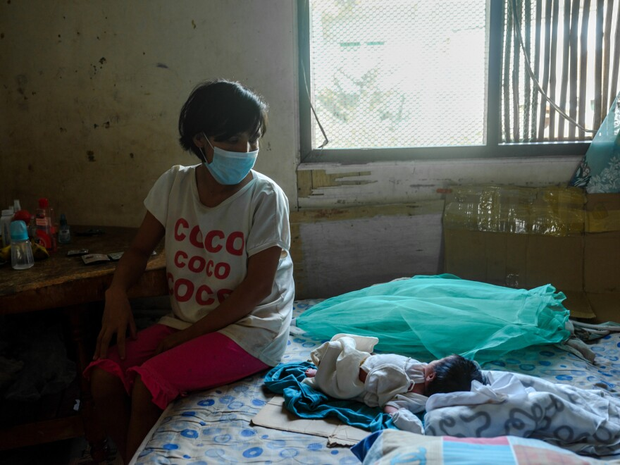 Jessa Tayombong sits with her baby, Josie. Even though home births are illegal in the Philippines, Tayombong delivered the child at home.
