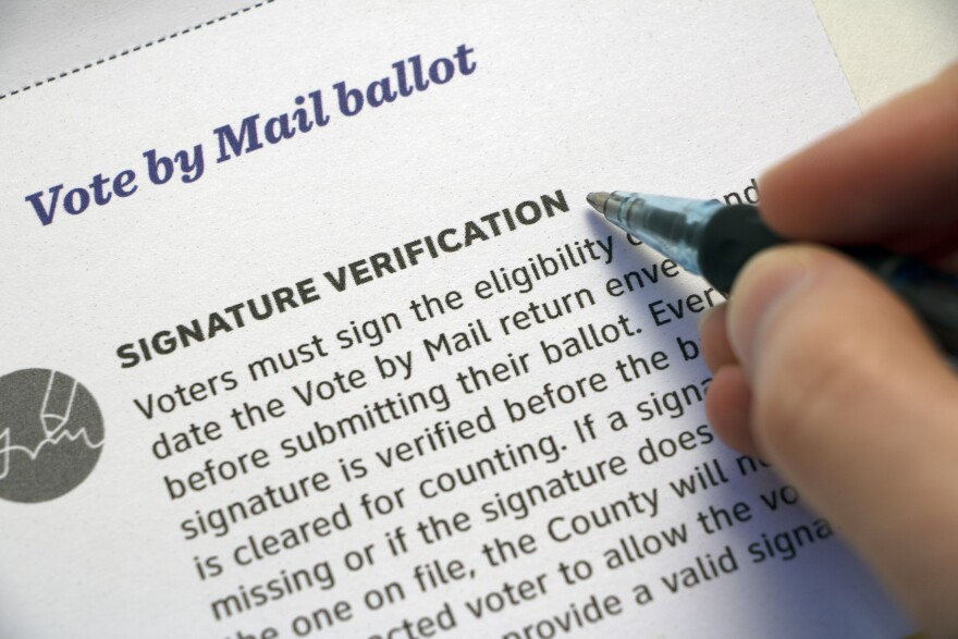 'Signature Verification' Mail Voting info and hand with pen