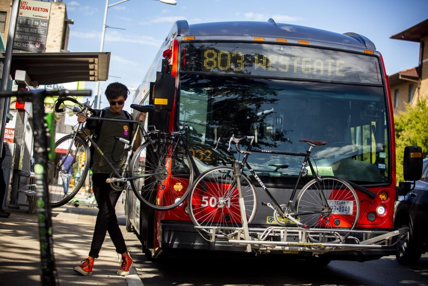 A Cap Metro rider removes a bicycle from the front of the bus.