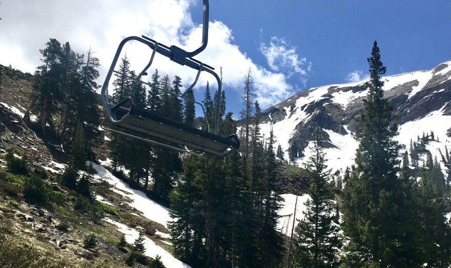 Photo of chairlift with snowy mountains in the background.
