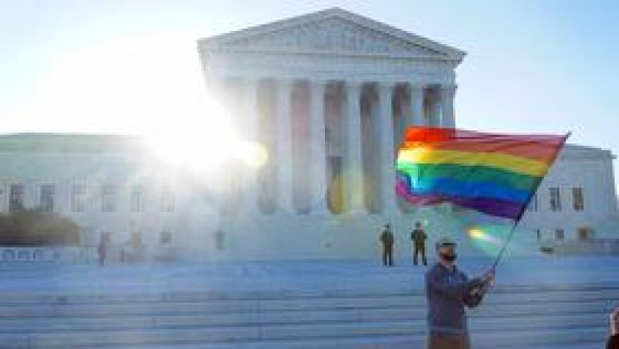 A man waves a rainbow flag in front of the United States Supreme Court.