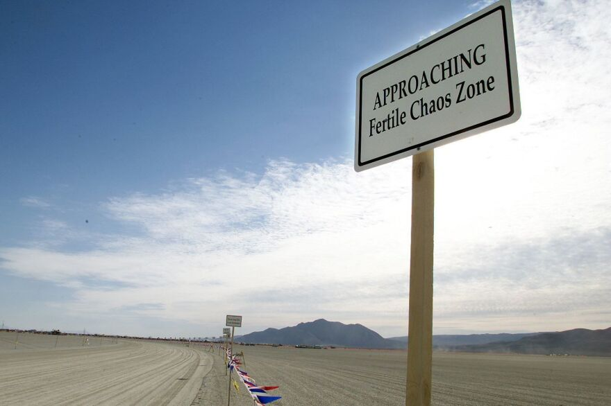 A sign is posted at the entrance checkpoint for the Burning Man festival in Nevada's Black Rock Desert in 2000. The festival's co-founder, Larry Harvey, died on Saturday at 70 after suffering a massive stroke.