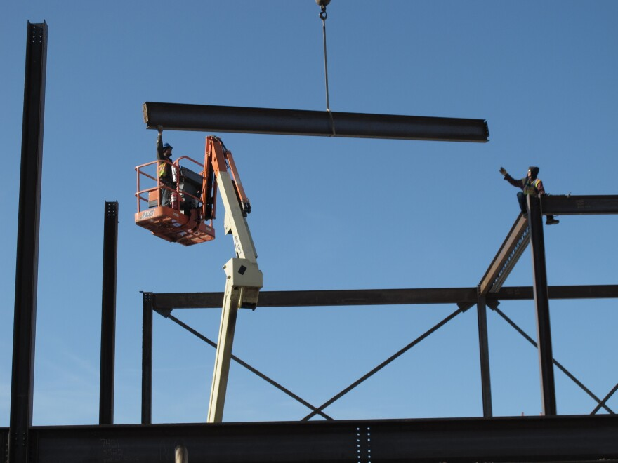 Construction workers ease a steel girder into place as part of a remodeling and expansion of the North Dakota State Penitentiary in Bismarck, N.D. An energy boom has helped the state maintain a budget surplus.