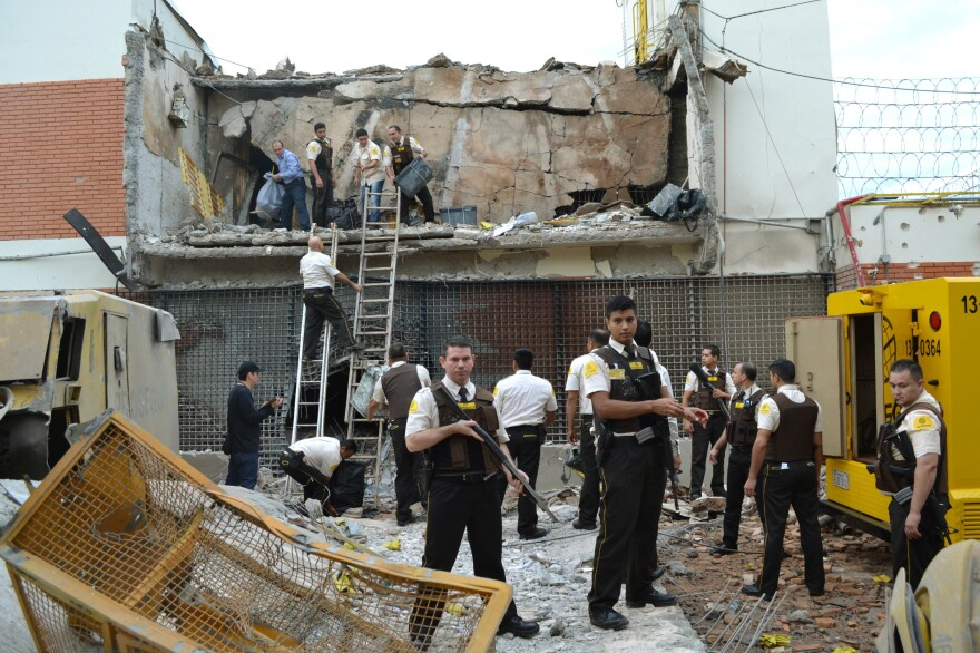 Guards and police inspect a vault that the assailants blew up early Monday morning in Ciudad del Este, Paraguay.