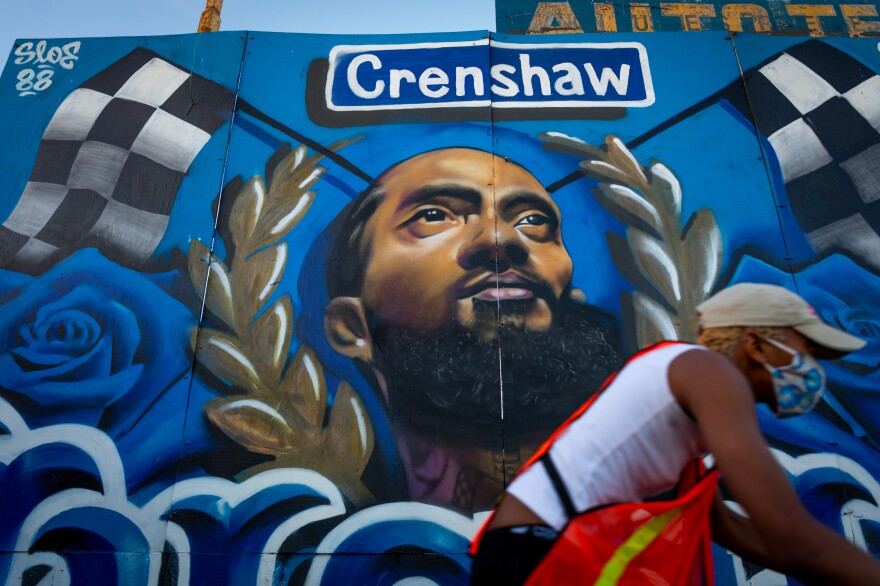 Los Angeles, CA � Residents pass by a mural on Slauson Avenue in Crenshaw Dec. 5, 2020. In the wake of Nipsey Hussle's March 2019 death, many murals of the beloved Los Angeles musician were painted in the Hyde Park neighborhood near his Marathon clothing store. The store and a large Nipsey mural in its alleyway are now fenced off but other nearby murals continue to draw local and visiting fans.