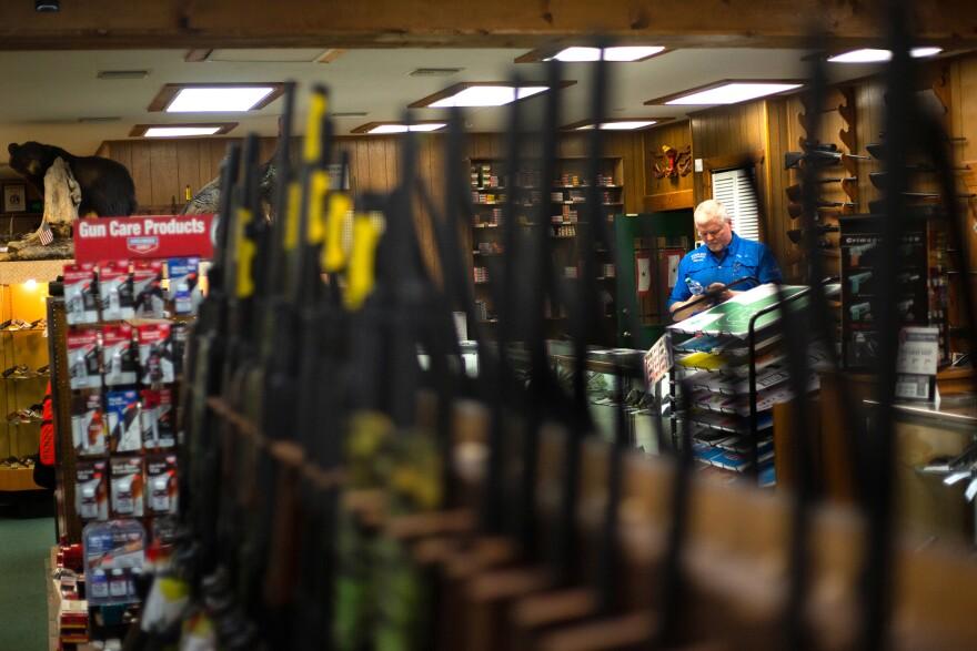 Jack Pickett shown behind guns in his store