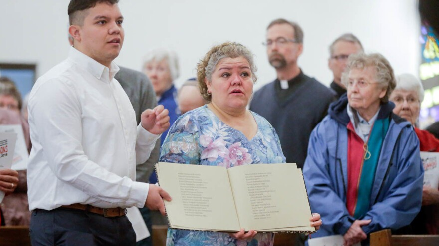 During a service at St. Bridget Catholic Church in Postville, Iowa, last year, Consuelo Lopez (center, right) and her son Pedro carry a book containing the names of those arrested and detained during a 2008 Immigration and Customs Enforcement raid on a local meat processing plant. Consuelo Lopez, who cut meat at the plant, was among those detained and deported.