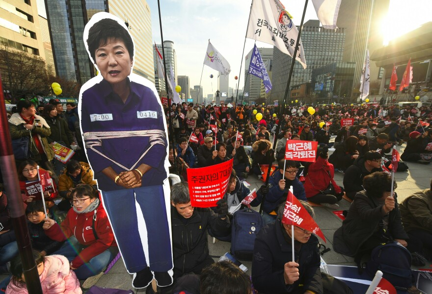Protesters carry a portrait of South Korea's President Park Geun-Hye during a rally against Park in central Seoul on Saturday. Hundreds of thousands of protestors marched in Seoul for the sixth straight week on December 3, to demand the ouster and arrest of scandal-hit President Park Geun-Hye ahead of an impeachment vote in parliament.