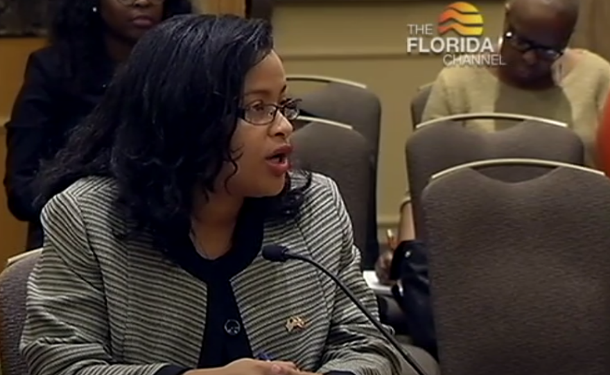 Renatha Francis stands at a podium, speaking to a panel of Florida lawmakers.
