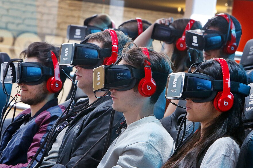 Visitors wear virtual reality glasses to watch a show on the first public day at the IAA car show in Frankfurt, Germany, Saturday, Sept. 16, 2017. (Michael Probst/AP)