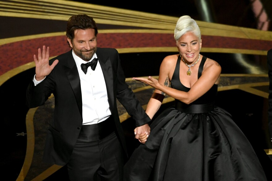 """Bradley Cooper and Lady Gaga address the crowd after performing onstage at the Academy Awards. Their song """"Shallow"""" later won the Oscar for original song."""