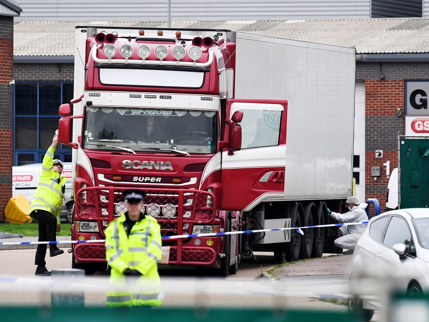 Police and forensic officers investigate a truck and refrigerated trailer where 39 bodies were discovered in Thurrock, England.