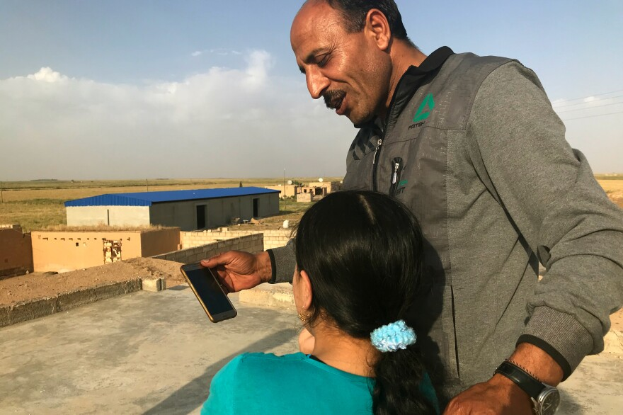 On the roof of his home, Mahmoud Rasho places a video call for Watfa, 10, to allow her to talk to her relatives in Canada. Her mother, who was also held captive by ISIS, has been admitted as a refugee in Canada.