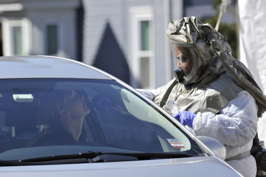 A medical professional takes samples from person at a drive-through coronavirus testing lab set up at Somerville Hospital in Somerville, Mass., on Wednesday.