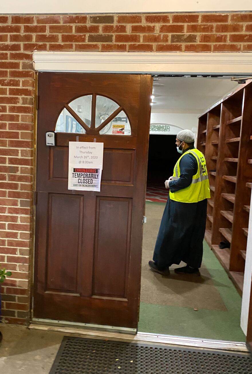 Imam Muhammad Khan stands inside the entrance of the Islamic Center of Charlotte, closed due to the coronavirus pandemic.
