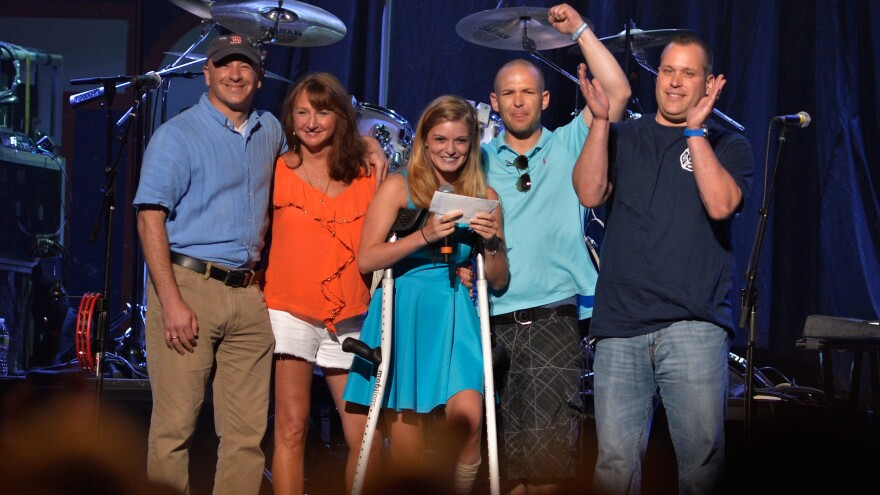 Marathon bombing victim Victoria McGrath (center) has died at age 23. She's seen here at a benefit concert in May 2013 with (from left) Bruce Mendelsohn, who applied a tourniquet to McGrath's leg after the Boston bombing; first responder Alicia Shambo, McGrath; first responder Tyler Dodd; and Boston firefighter Jimmy Plourde.