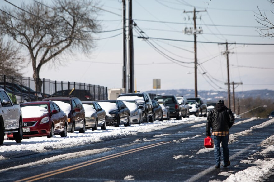 Un peatón lleva un contenedor de gasolina a lo largo de una calle nevada en el sur de Austin el martes.