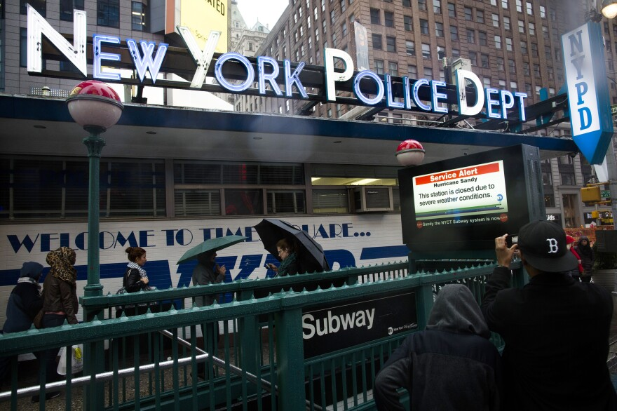 Pedestrians pass a New York Police Department station beside a closed subway entrance at Times Square on Monday.