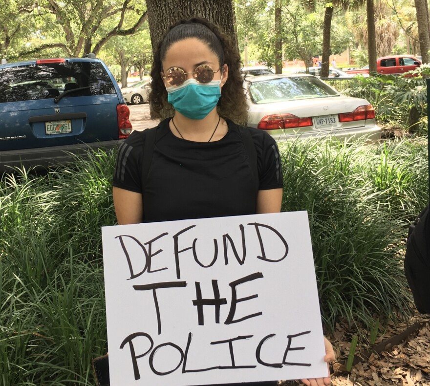 Samar Perez holds a defund the police sign