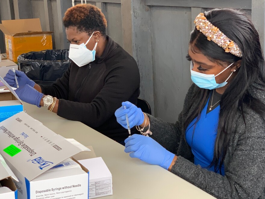 Two female health workers sit at a folding table preparing syringes with coronavirus vaccines at a Hillsborough County vaccination site.