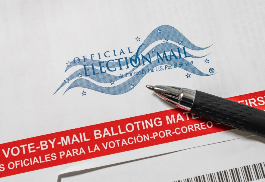 Pictured here is an envelope for a vote-by-mail ballot. A pen is on top of the envelope.