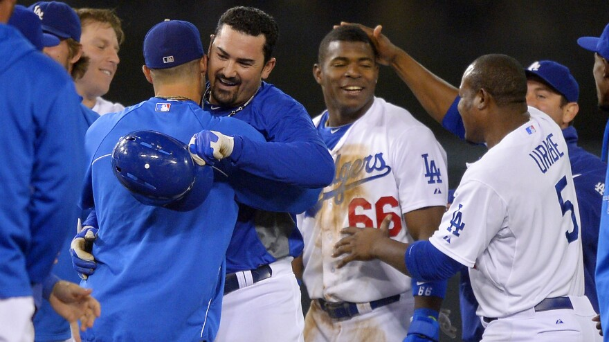 Los Angeles Dodgers' Adrian Gonzalez (center left, holding helmet) is congratulated by teammates along with Yasiel Puig (No. 66) after Gonzalez hit a game-winning RBI double and Puig scored during the 12th inning of their game against the New York Mets on Wednesday.