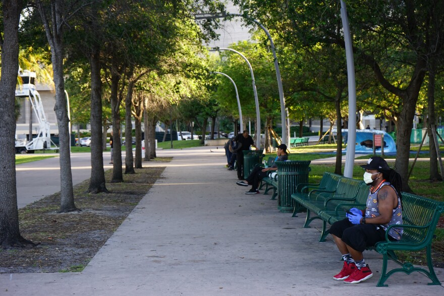 People sit apart from each other on park benches in downtown Miami.