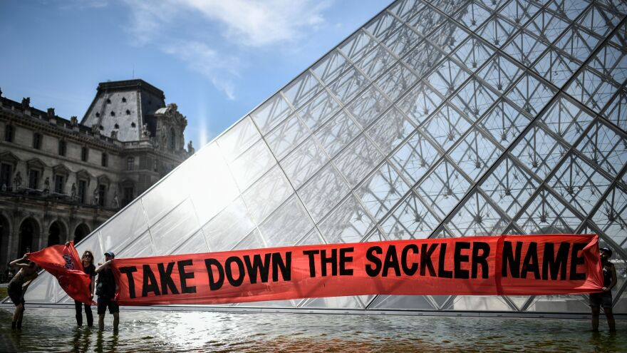 "Activists raise a banner reading ""Take down the Sackler name"" during a demonstration earlier this year in front of the Louvre Pyramid in Paris."