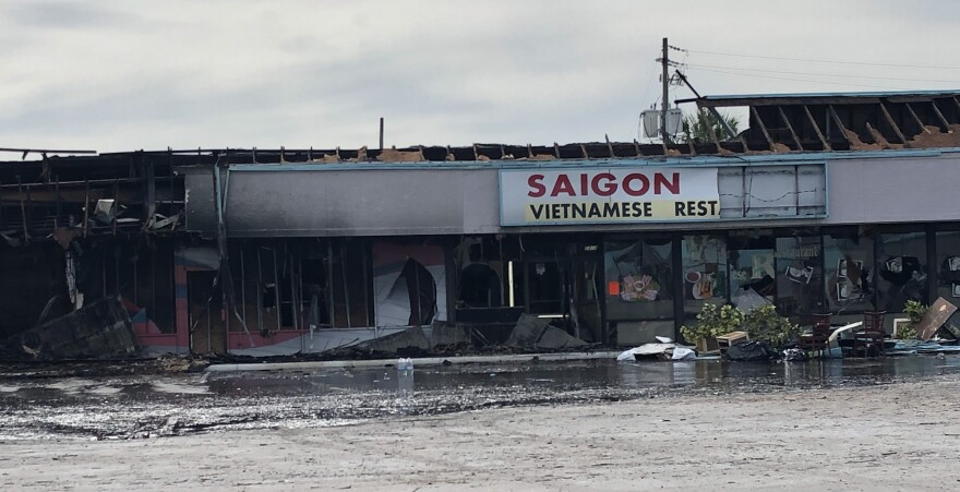 A charred building with debris and puddles of water in front of it.