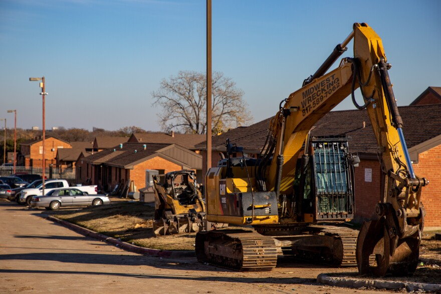 Heavy construction machinery stands idle on a street of red brick apartment buildings.