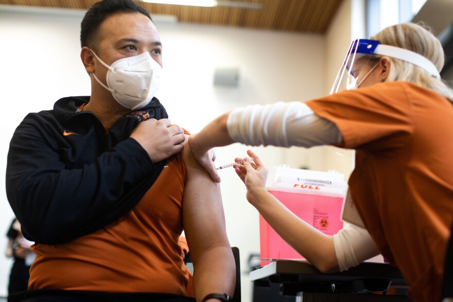 UT-Austin football athletic trainer Johnnathan Tran receives the COVID-19 vaccine Pfizer BioNTech during injections to healthcare workers at Dell Medical School on Dec. 15, 2020. (Gabriel C. Pérez/KUT News)