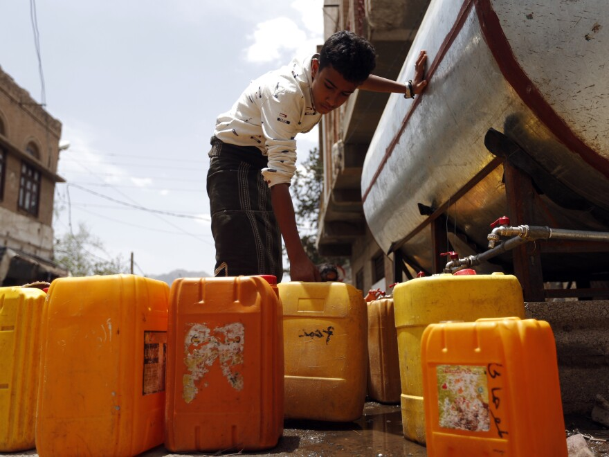 """A Yemeni boy fills jerrycans with safe drinking water from a donated water tank in Sanaa earlier this month. The collapse of Yemen's infrastructure after more than two years of war between the Saudi-backed government and Shiite rebels who control the capital has made for a """"perfect storm for cholera,"""" according to a World Health Organization official."""