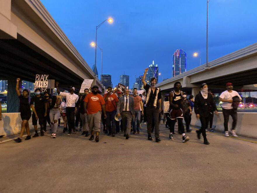 A photo of a group of people, holding protest signs, walking onto a highway at nightfall.