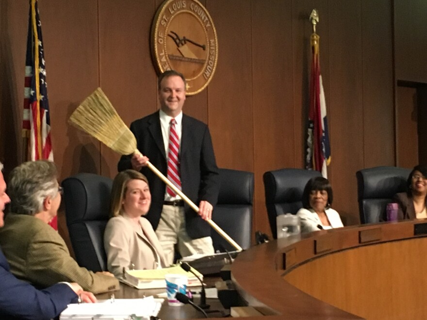 St. Louis County Executive Sam Page hold a broom he received from Councilman Mark Harder during a May 7, 2019, council meeting. Page took over as county executive as Steve Stenger's resignation.