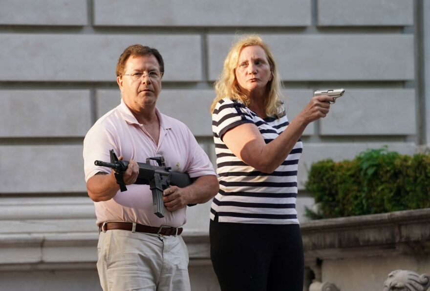 Personal injury attorneys Mark and Patricia McCloskey emerge Sunday evening from their Portland Place house pointing guns at protesters who were on their way to protest in front of St. Louis Mayor Lyda Krewson's house.| 6/28/20