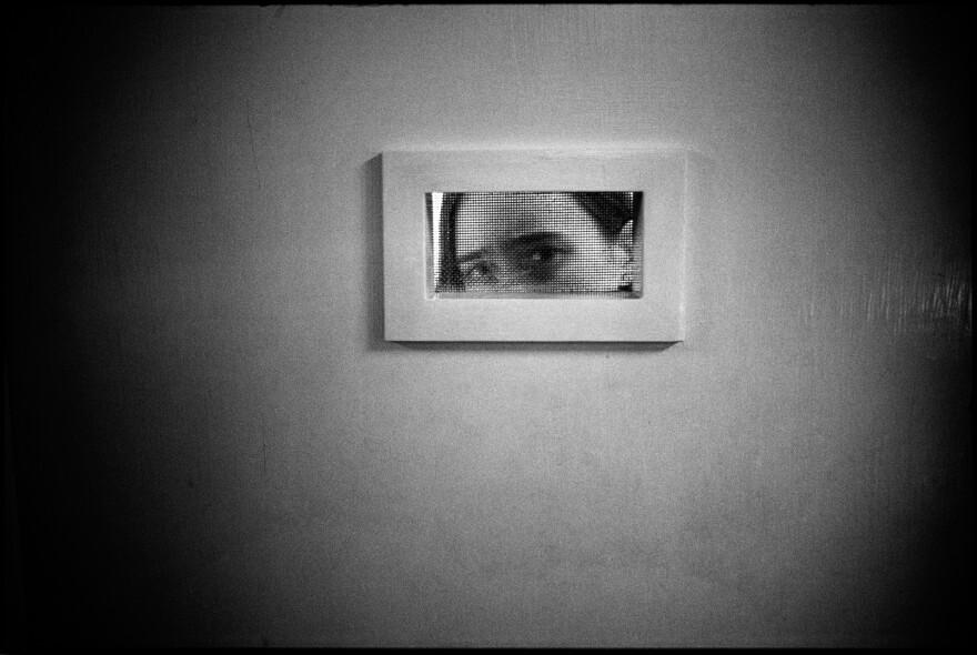 Tommie peeking out of her room, Ward 81, Oregon State Hospital. Salem, Oregon, 1976.