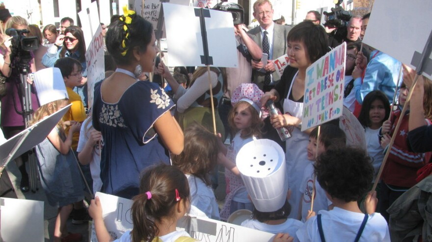 """Moms and their kids protest a proposed ban on homemade food at bake sales in New York City schools at a rally near City Hall in 2010. One sign read, """"I wanna get obese on my terms. No junk food."""""""