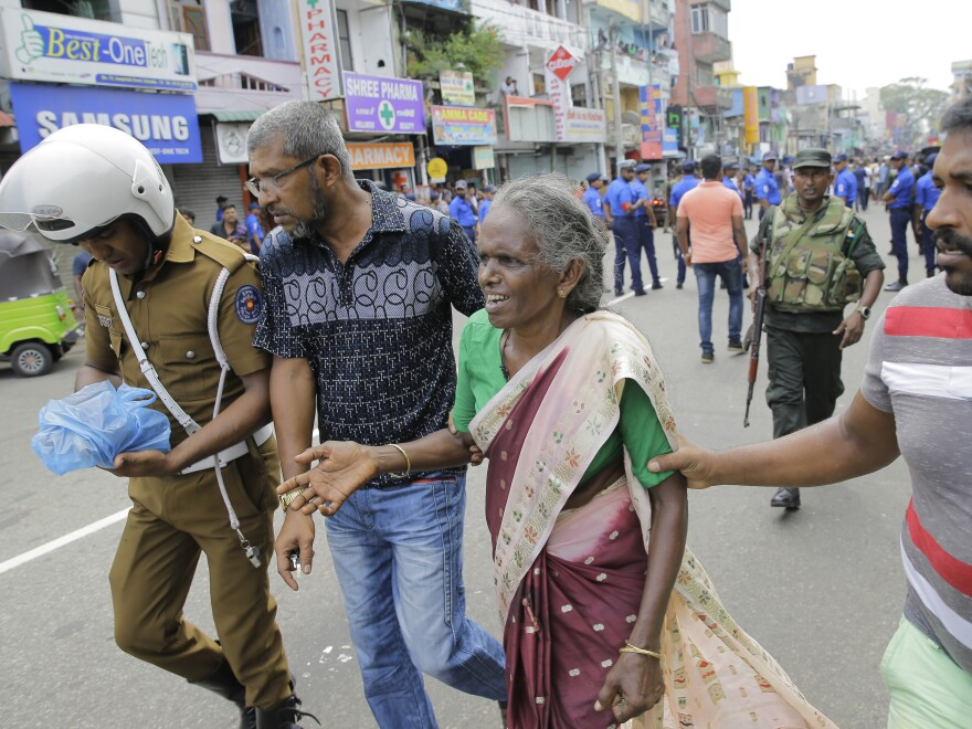 In Colombo, a woman is helped near St. Anthony's Shrine, the site of one of multiple explosions in Sri Lanka on Easter Sunday.
