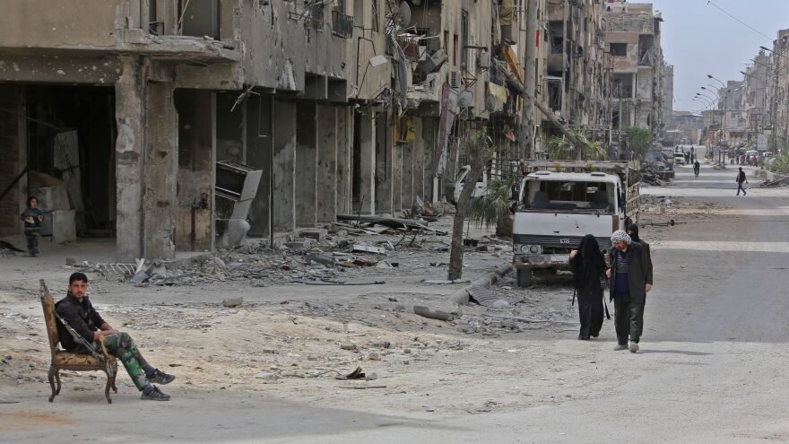 Civilians walk in the formerly rebel-held Syrian town of Douma, on the outskirts of Damascus, on Tuesday. The Syrian army declared that all anti-regime forces have left Eastern Ghouta, following a blistering two-month offensive, including an alleged chemical weapons attack. It's not clear when international inspectors will enter Douma to evaluate the site.