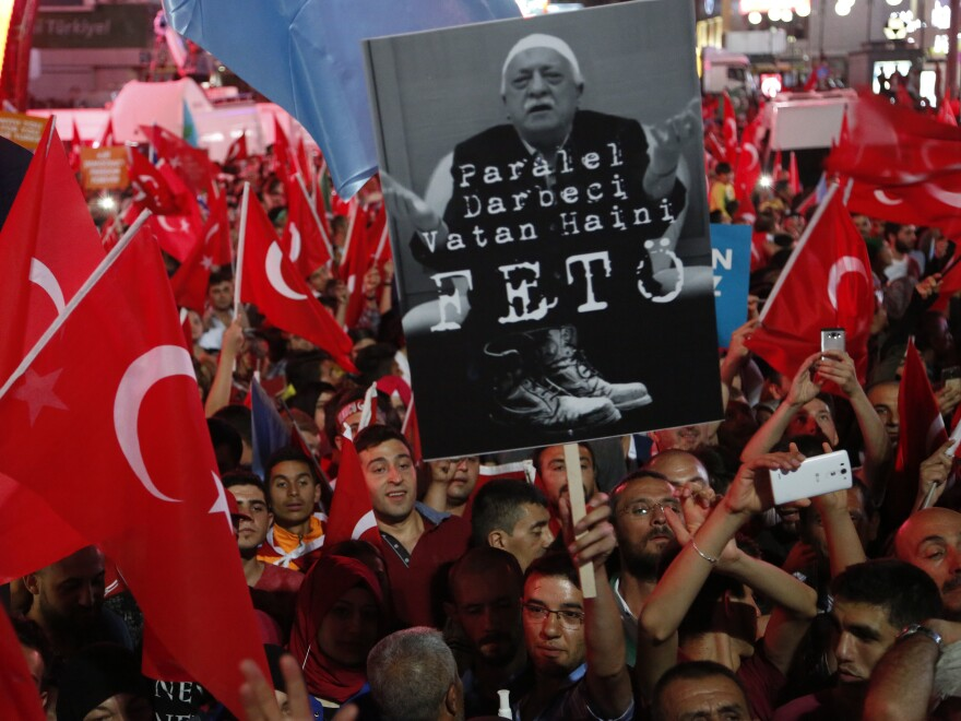 "Pro-government supporters in Ankara wave Turkish flags and hold signs showing Fethullah Gulen on July 20. The sign says ""The coup nation traitor, FETO."" FETO stands for ""Fethullah Terrorist Organization."""
