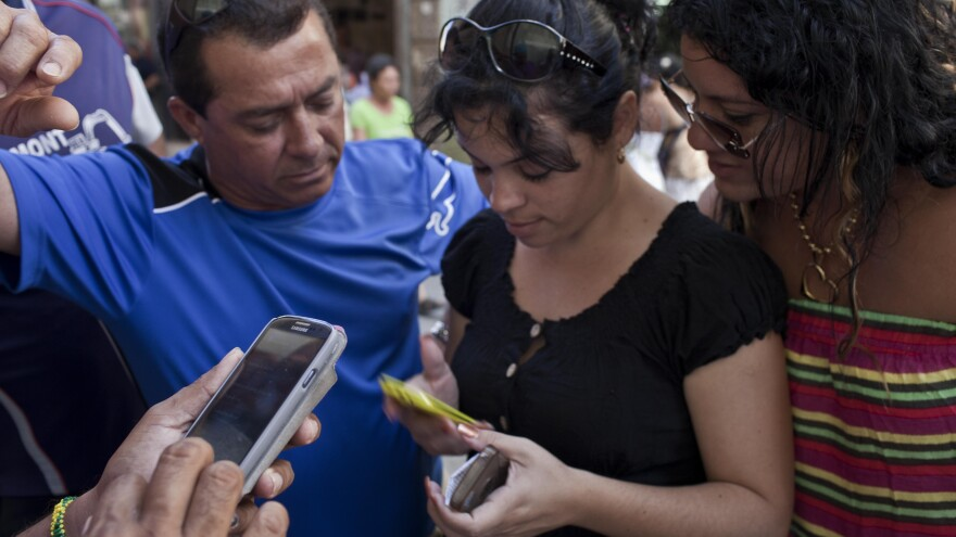 Cubans try to connect to the ETECSA server during a May 9 service outage as they wait with other customers outside the offices of the state telecom monopoly in Havana, Cuba. Cuba's government has blamed technological problems on a U.S. embargo. Critics of the government have said it deliberately strangles the Internet to mute dissent. Changing U.S.-Cuba relations may prove who's right.