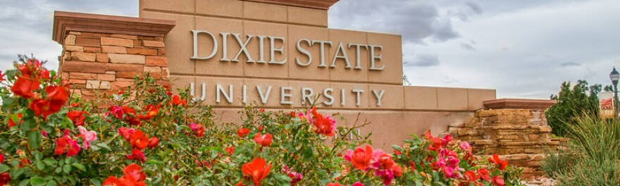 A photo of a sign that says 'Dixie State University' with pink and red flowers planted around it.