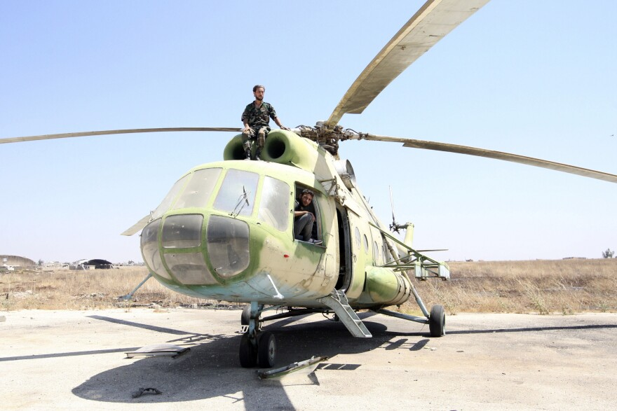The U.S. is considering adding helicopters to its list of potential targets of a military strike. Here, rebel fighters are seen on a Russian-made helicopter seized from the Syrian army at the Minnig Military Airport near the Turkish border on Aug. 11.
